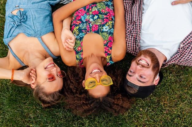 Draufsicht der stilvollen glücklichen jungen freunde, die auf gras im park liegen