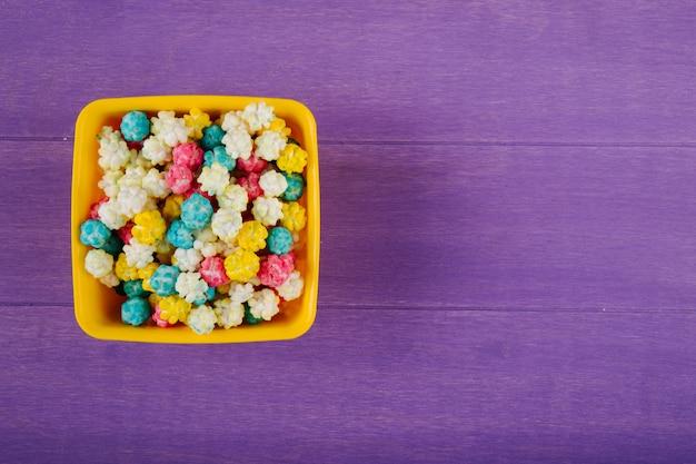 Draufsicht der süßen bunten zuckersüßigkeiten in einer schüssel auf lila hölzernem hintergrund mit kopienraum