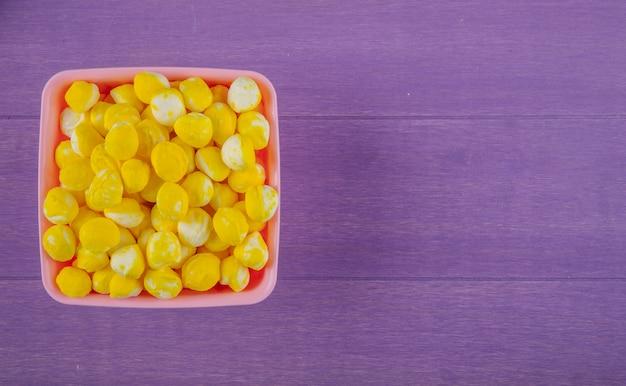 Draufsicht der süßen gelben bonbons in einer schüssel auf lila hölzernem hintergrund mit kopienraum