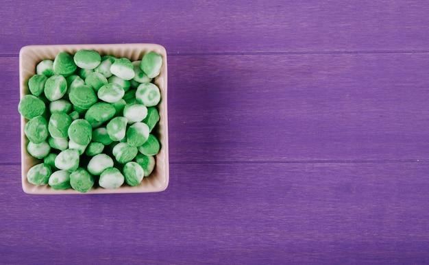 Draufsicht der süßen grünen bonbons in einer schüssel auf lila hölzernem hintergrund mit kopienraum