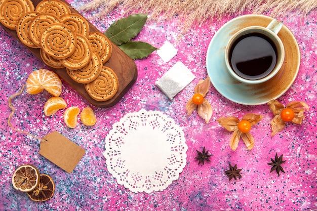 Draufsicht der süßen kekse mit tasse tee und mandarinen auf der rosa oberfläche
