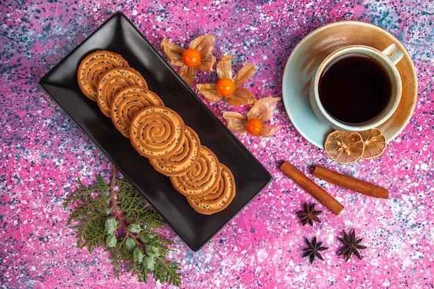 Draufsicht der süßen kekse mit zimt und tasse tee auf hellrosa oberfläche