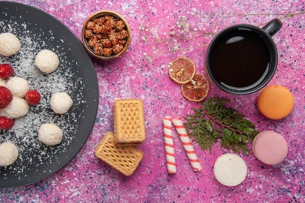 Draufsicht der süßen kugeln der köstlichen kokosnussbonbons mit französischen macarons auf der rosa oberfläche