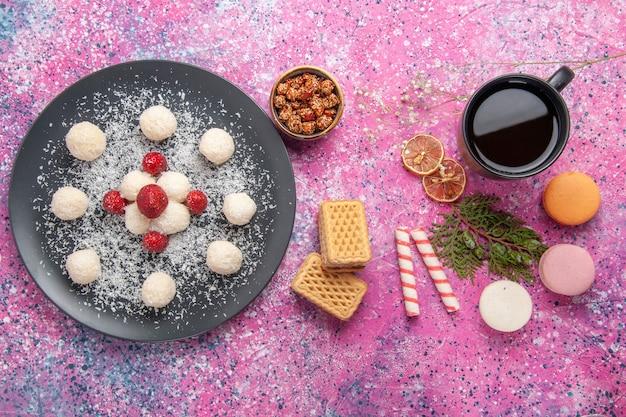 Draufsicht der süßen kugeln der köstlichen kokosnussbonbons mit französischen macarons auf hellrosa oberfläche