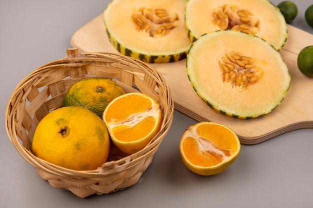 Draufsicht der süßen scheiben der melone der melone mit feijoas lokalisiert auf einem hölzernen küchenbrett mit mandarinen auf einem eimer auf einer grauen wand