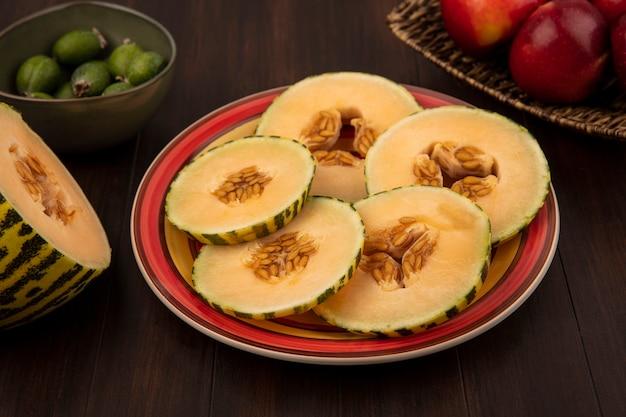 Draufsicht der süßen scheiben der melone melone auf einem teller mit feijoas auf einer schüssel mit äpfeln auf einem weidentablett auf einer holzwand
