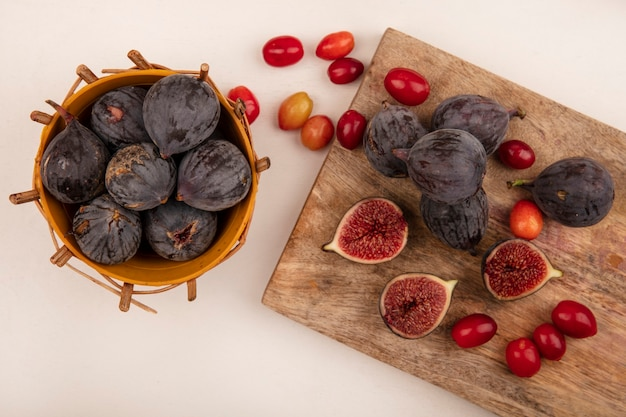 Draufsicht der süßen schwarzen feigen auf einem eimer mit schwarzen feigen und kornelkirschen, die auf einem hölzernen küchenbrett auf einer weißen wand lokalisiert werden