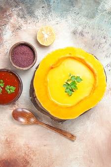 Draufsicht der suppenlöffel-zitronen-kürbissuppe auf den brettsaucengewürzen