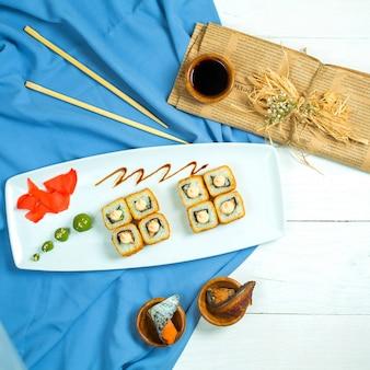 Draufsicht der sushi-rolle der traditionellen japanischen küche mit garnelen-avocado und frischkäse auf blau und weiß