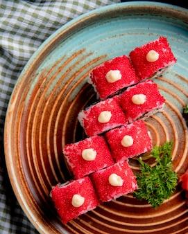 Draufsicht der sushi-rolle mit krabbenavocado bedeckt mit rotem kaviar mit ingwer und wasabi auf einem teller