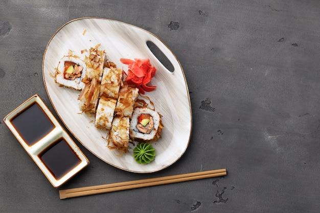 Draufsicht der sushi-rolle mit thunfischspänen auf teller serviert
