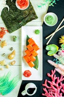 Draufsicht der sushi-satzrollen mit krabbenfleisch-frischkäse und avocado im kaviar des fliegenden fisches mit sojasauce auf bambusblatt