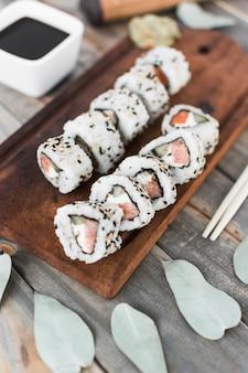 Draufsicht der sushirolle auf hölzernem behälter mit sojasoße und essstäbchen