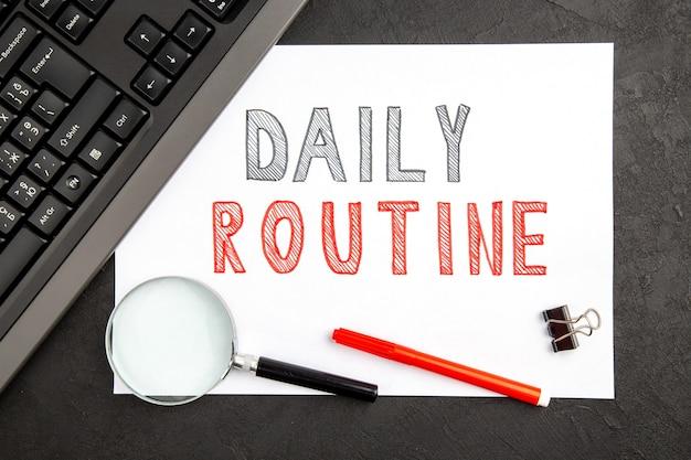 Draufsicht der täglichen routine, die auf leerem papier auf dunkler oberfläche schreibt