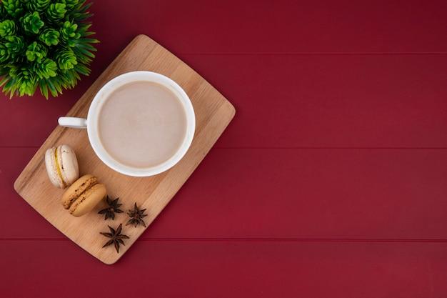Draufsicht der tasse cappuccino mit macarons auf einem schneidebrett auf einer roten oberfläche