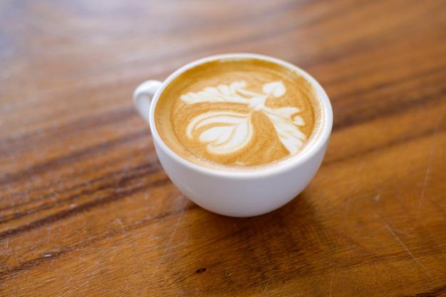 Draufsicht der tasse der heißen lattekunst auf hölzernem tischhintergrund