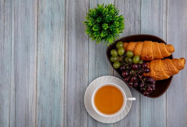 Draufsicht der tasse des heißen wirbels und der croissants-trauben in der schüssel mit pflanze auf hölzernem hintergrund mit kopienraum