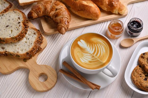 Draufsicht der tasse kaffee latte mit brot oder brötchen, croissant und bäckerei auf weißem holztisch