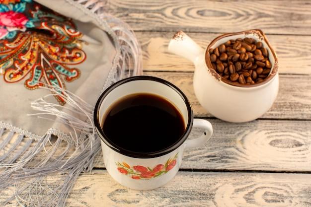 Draufsicht der tasse kaffee mit braunen kaffeesamen auf dem hölzernen schreibtisch