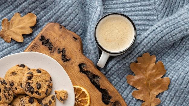 Draufsicht der tasse kaffee mit pullover und herbstlaub