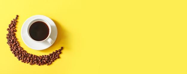 Draufsicht der tasse kaffee und der kaffeebohnen auf minimalem gelbem horizontalem hintergrund