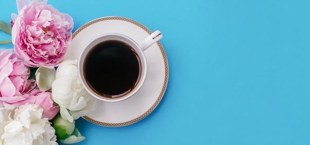 Draufsicht der tasse kaffee und der pfingstrosenblumen