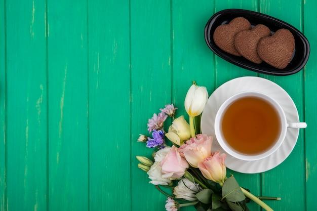 Draufsicht der tasse tee auf untertasse und herzförmigen keksen in länglicher schüssel mit blumen auf grünem hintergrund mit kopienraum