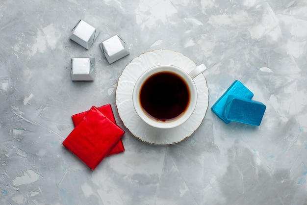 Draufsicht der tasse tee heiß in weißer tasse auf glasplatte mit silberner und farbiger packung pralinen auf hellem schreibtisch, tee trinken süße keksteatime