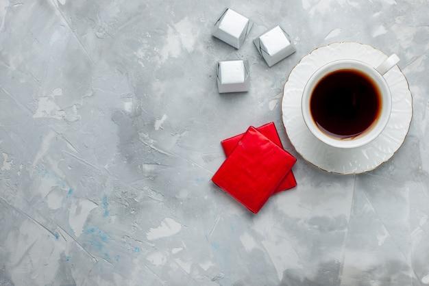 Draufsicht der tasse tee heiß in weißer tasse auf glasplatte mit silberverpackung pralinen auf weißem, teegetränk süßer schokoladenkeks