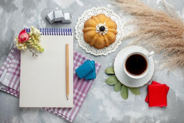 Draufsicht der tasse tee heiß in weißer tasse mit kuchen-notizblock-pralinen auf leichtem tee-schokoladen-bonbonkuchen