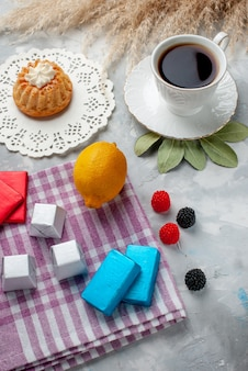 Draufsicht der tasse tee heiß innerhalb der weißen tasse mit kuchen zitronenschokoladen auf hellem schreibtisch, tee pralinenkuchen