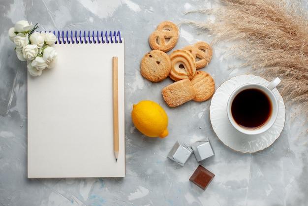 Draufsicht der tasse tee heiß mit schokoladenzitrone und keksen auf licht, kekssüßigkeit schokoladentee-kekse süß