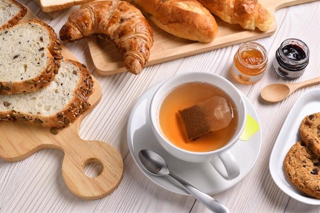 Draufsicht der tasse tee mit brot oder brötchen, croissant und bäckerei auf weißem holztisch