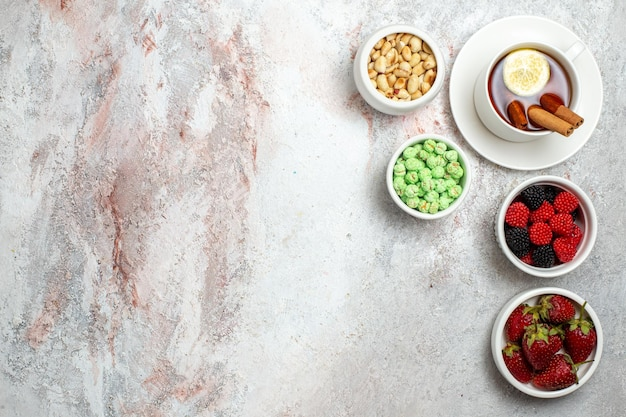 Draufsicht der tasse tee mit erdbeeren und nüssen auf weißer oberfläche