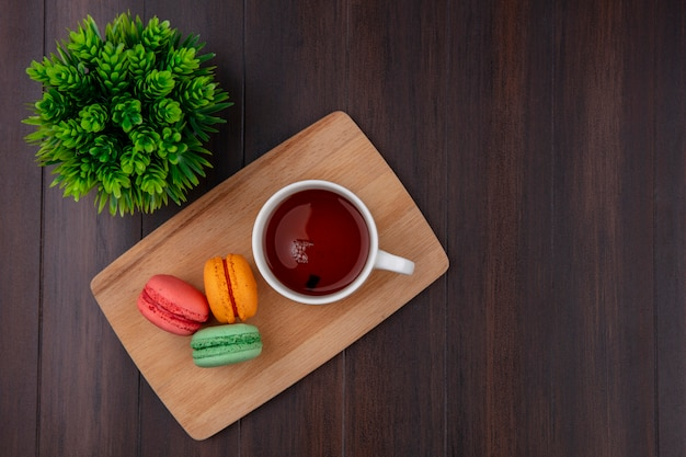Draufsicht der tasse tee mit farbigen macarons auf einem schneidebrett auf einer holzoberfläche