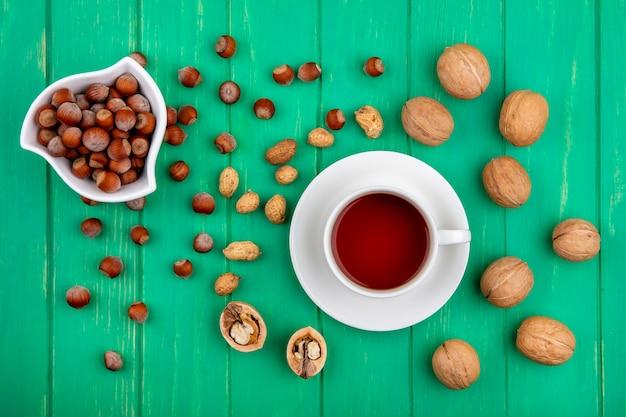 Draufsicht der tasse tee mit haselnüssen in einer schüssel walnüssen und erdnüssen auf einer grünen oberfläche