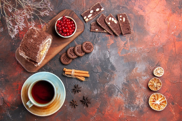 Draufsicht der tasse tee mit keksrolle auf dunkler oberfläche