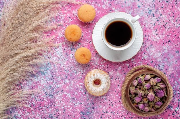 Draufsicht der tasse tee mit kleinen kuchen auf der rosa oberfläche