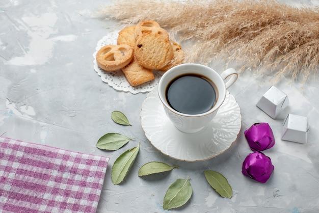 Draufsicht der tasse tee mit köstlichen kleinen keksen pralinen auf hellem schreibtisch, kekskeks süßer teezucker