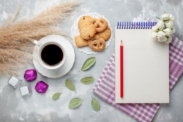Draufsicht der tasse tee mit köstlichen kleinen keksen pralinen auf hellgrauem, süßem teezucker des kekskekses