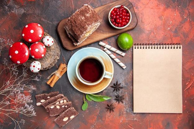 Draufsicht der tasse tee mit kuchen und keksrolle auf dunkler oberfläche