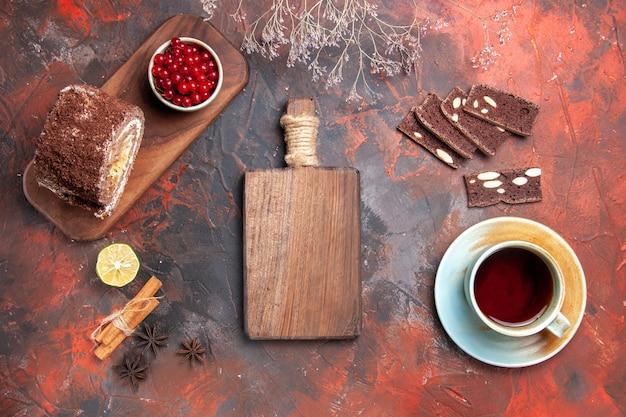 Draufsicht der tasse tee mit kuchen- und keksrollen auf dunkler oberfläche