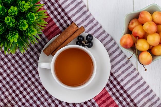 Draufsicht der tasse tee mit schwarzen zimt johannisbeeren und weißen kirschen auf einem rot karierten handtuch auf einer weißen oberfläche