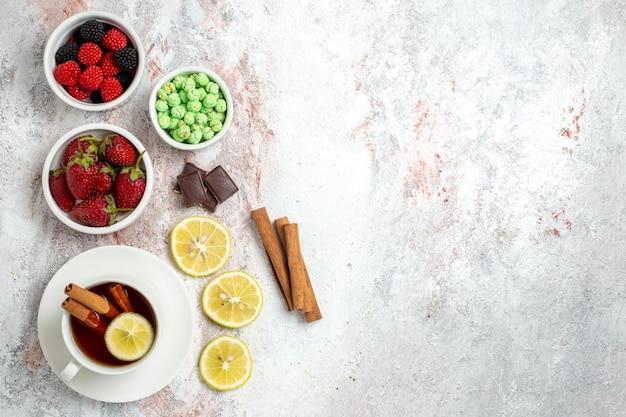 Draufsicht der tasse tee mit süßigkeiten und erdbeeren auf weißer oberfläche