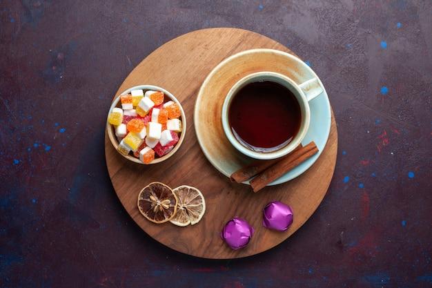 Draufsicht der tasse tee mit süßigkeiten und zimt auf der dunklen oberfläche