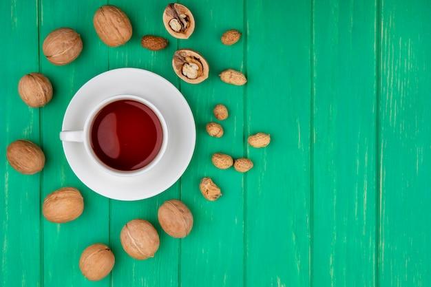 Draufsicht der tasse tee mit walnüssen und erdnüssen auf einer grünen oberfläche