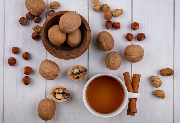 Draufsicht der tasse tee mit zimt-haselnuss-walnüssen und erdnüssen auf einer weißen oberfläche