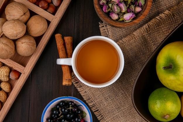 Draufsicht der tasse tee mit zimtäpfeln und nüssen auf einer holzoberfläche