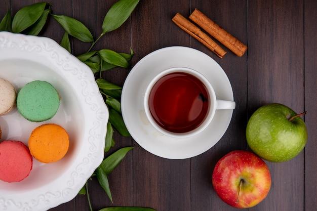 Draufsicht der tasse tee mit zimtfarbenen macarons und äpfeln auf einer holzoberfläche