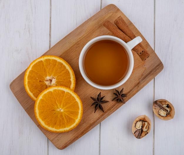 Draufsicht der tasse tee mit zimtscheiben der orange auf einem brett mit walnüssen auf einer weißen oberfläche